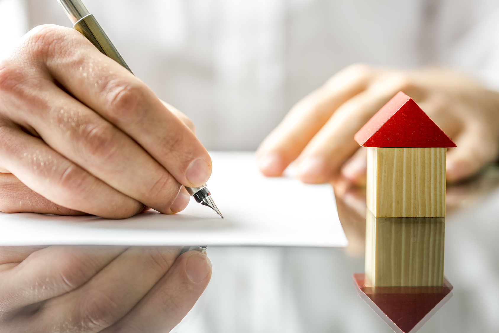 Conceptual image of a man signing a mortgage or insurance contract or the deed of sale when buying a new house or selling his existing one with a small wooden model of a house alongside