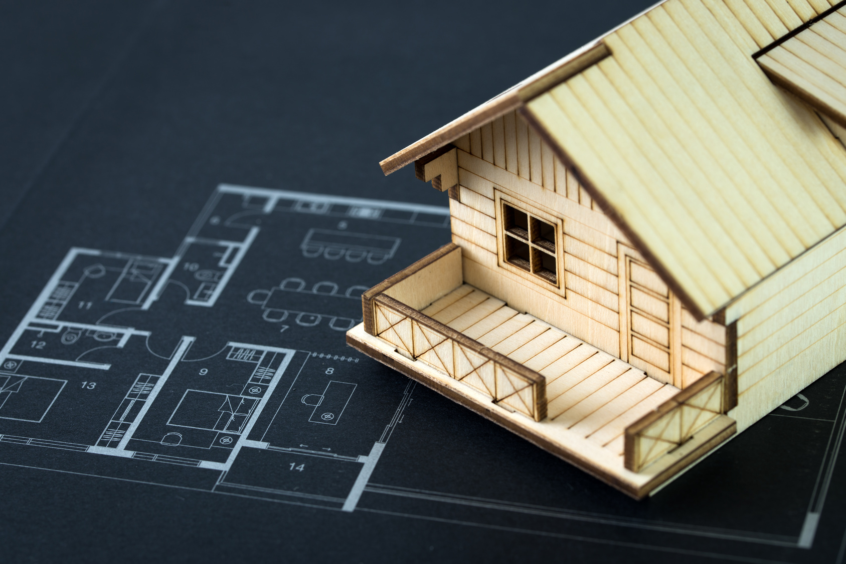 Miniature house rest on top of home blueprint